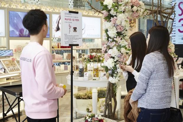 [아리따움]플래그쉽 스토어를 찾은 고객들이 마몽드존에서 '복숭아꽃 스킬 이벤트에 참여하고 있다..jpg