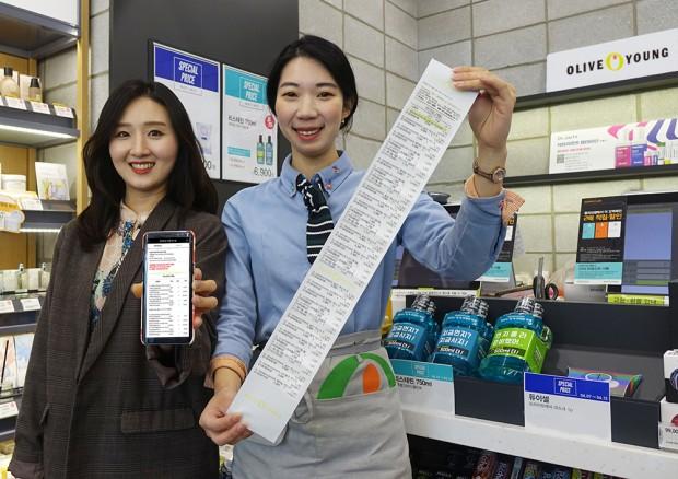 [CJ올리브네트웍스_보도자료] 올리브영 매장에서 직원이 스마트영수증과 종이영수증을 비교하고 있는 모습.jpg