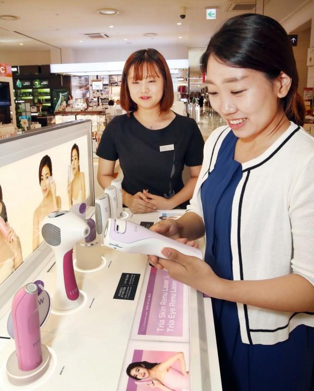 [트리아]매장에서 트리아 스킨 리뉴 레이저를 보고 있는 고객 모습.jpg